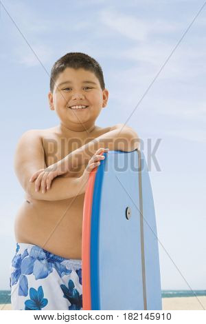 Hispanic boy holding boogie board