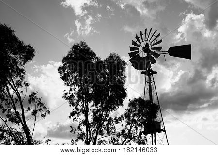 Silhouette of a working vintage country Windmill in sunset light or twilight