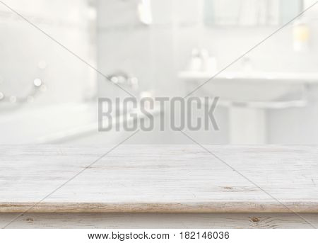 Wooden table in front of blurred bathroom interior as background