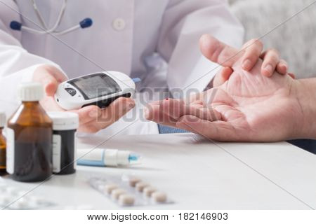 the doctor measuring blood sugar on background white table