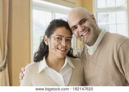 Hispanic couple smiling in livingroom