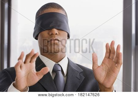 Mixed race businessman wearing blindfold