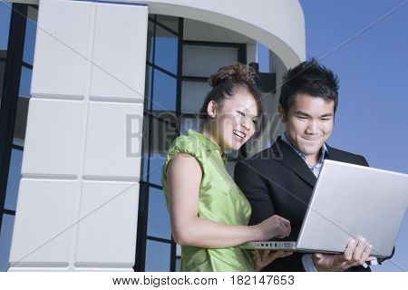 Asian business people looking at laptop outdoors