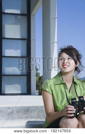 Asian businesswoman sitting outdoors with binoculars