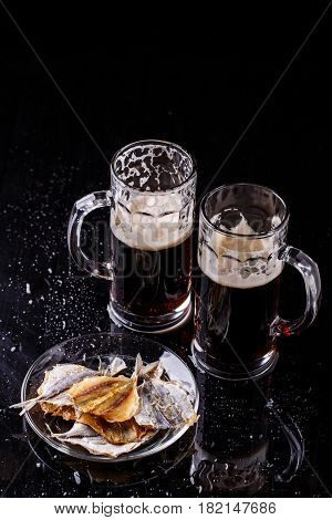 Photo of two glasses of beer with plate of fish on black table