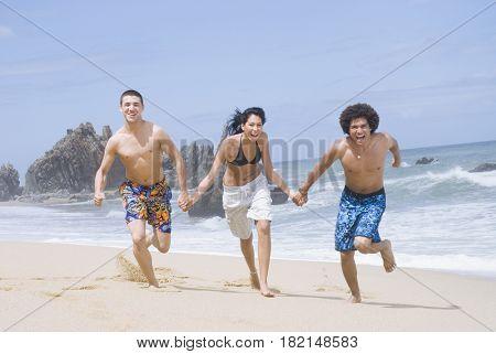 Multi-ethnic friends running on beach