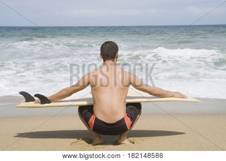 Hispanic man with surfboard at beach