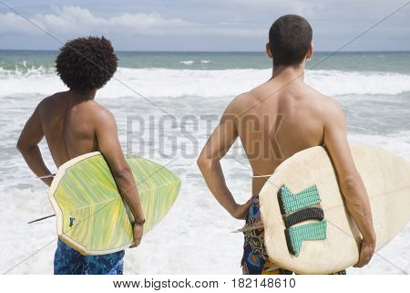 Friends at beach with surfboards