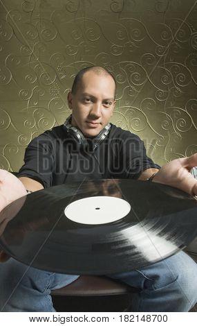 Hispanic man holding vinyl record