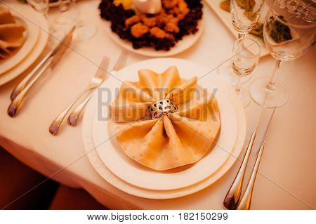 Table setting at a wedding banquet. Decoration flowers. A close-up of a plate with cutlery.