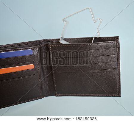 Leather wallet with credit cards and a small house. Buying house with credit and mortgage concept