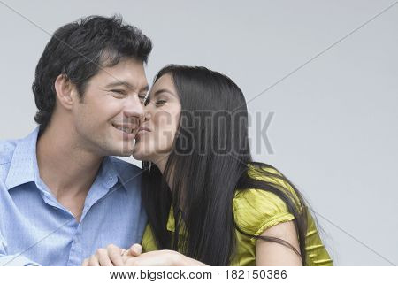 Hispanic woman kissing boyfriend