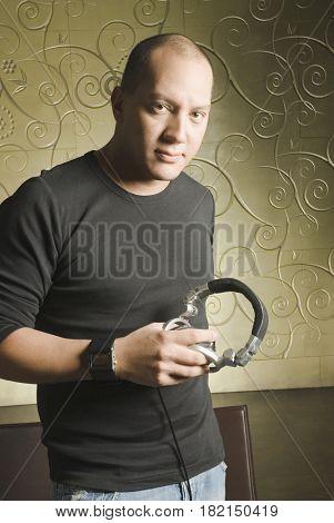 Hispanic man holding headphones