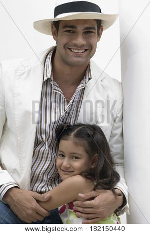 Hispanic father hugging smiling daughter