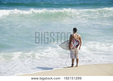Hispanic teenager at beach with surfboard
