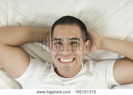 Smiling Hispanic man laying in bed