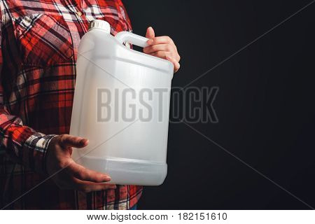 White unlabeled plastic 5 liters tank canister in female hand chemistry and chemical liquids mock-up container