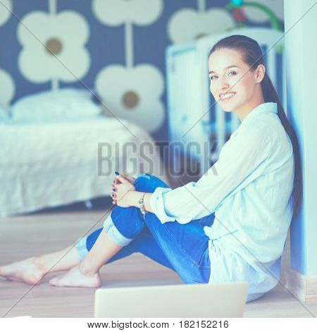 Young woman sitting on the floor near childrens cot