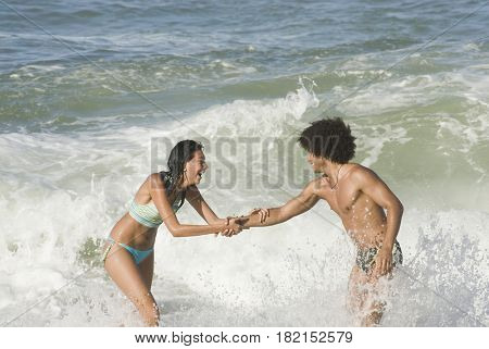Multi-ethnic couple playing in ocean