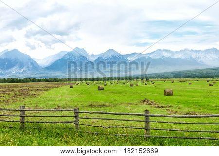 high mountains with snowy peaks, summer, valley, field, haystacks, Arshan Tunkinsky valley Irkutsk oblast