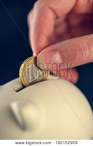 Depositing one euro coin into piggy coin bank for saving close up of female hand with european union currency