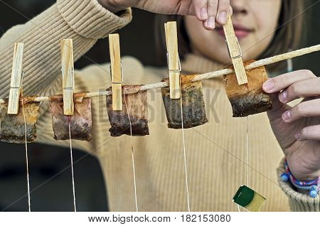 Girl is hanging used tea bags for drying and multiple use on the clothesline with clothes pegs