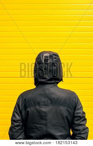 Facing problems and challenging obstacles in life woman in hooded winter jacket in front of the wall