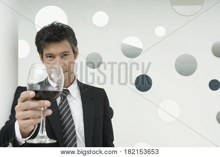 Hispanic businessman drinking wine