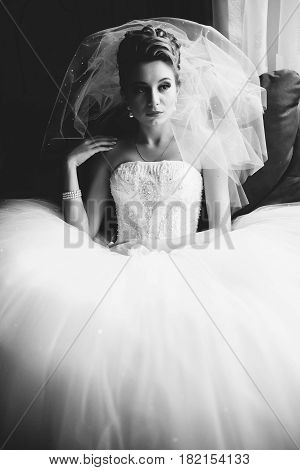 Bride Sits In A Big Chair Drowning In A Dress