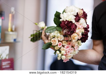 Persons holds bouquets made of pink white and wine-colored flowers