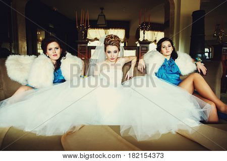A look from afar on bride and bridesmaids sitting on the couch in provoking manner