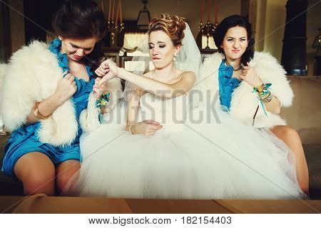 Bride shows thumb down looking in bridesmaid's decollete