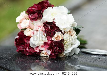 Bouquet of wine-colored and white flowers lies on a black car