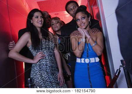 Glamorous women flirting at nightclub entrance