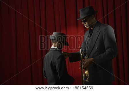 African man and boy in suits holding trumpet