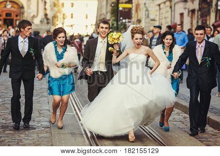 Bride with warlike spirit walks along the tramways with groom and friends