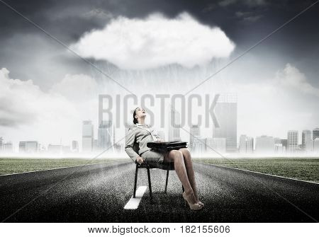 Young businesswoman with suitcase sitting on chair under rain