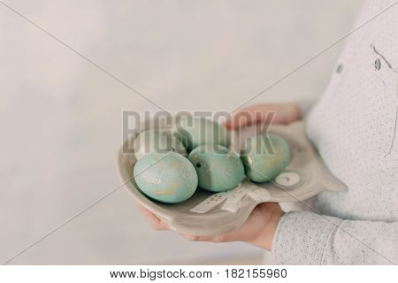 A small child in the hands of a plate with Easter blue eggs
