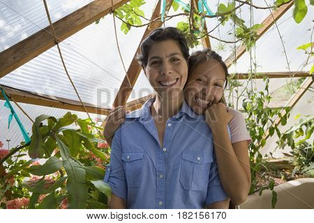 Mother and daughter hugging in conservatory
