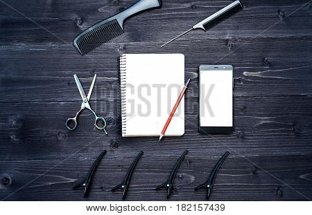 Hairdresser tools on wooden background. Blank card with barber tools flat lay. Top view on wooden table with scissors comb and hairclips with empty notebook pencil and phone free space
