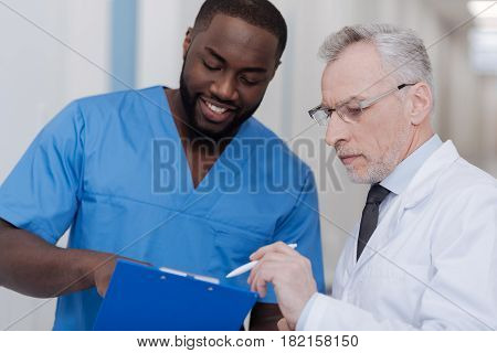 Valuing your experience. Curious happy African American intern standing in the clinic while holding folder and listening to the advice of the experienced doctor
