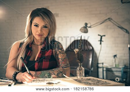 Portrait of smiling female with tattoo drawing tattoo image at desk. She looking at camera