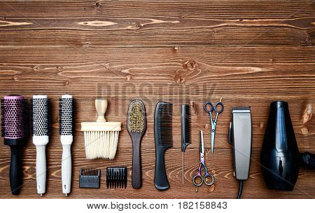 Hairdresser tools on wooden background. Top view on wooden table with scissors comb hairclipper hairbrushes and hairdryer free space. Barbershop poster
