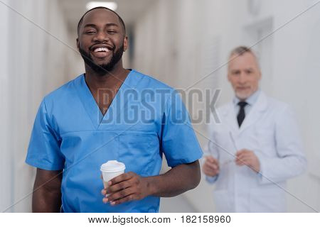Ready to give discover new horizons. Happy cheerful young African American intern standing in the clinic and holding cup of coffee while aged colleague standing in the background