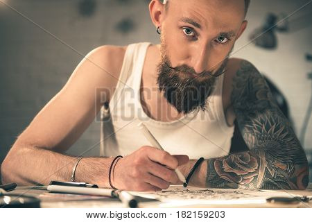 Serene male with tattoo drawing image at desk. He looking at camera. Portrait