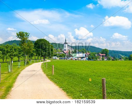 Summer landscape with lush green meadow, country road and white rural church. Prichovice, Northern Bohemia, Czech Republic, Europe.