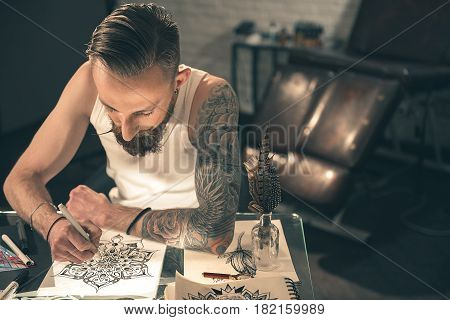 Top view of serene bearded male making tattoo image at desk in apartment. Creativity concept