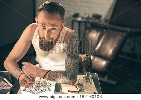 Top view of calm bearded man painting tattoo picture at table in room. Inspiration concept