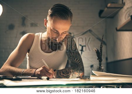 Portrait of Serene bearded male artist painting pictures while sitting at table
