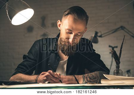 I have inspiration. Portrait of cheerful man making images while locating at desk